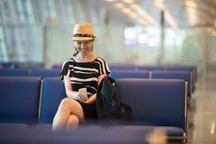 Femme à l'aide du téléphone portable dans le salon de attente d'aéroport Images libres de droits