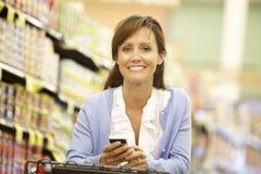 Femme à l'aide du téléphone portable dans le supermarché photos stock