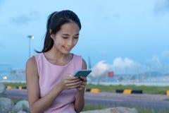 Femme à l'aide du téléphone portable en ligne dans la voie d'avion le soir Images stock