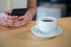 Femme à l'aide du téléphone portable et d'une tasse de café sur la table dans le café Photo libre de droits