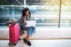 Femme à l'aide du téléphone portable et de l'ordinateur portable à l'aéroport se reposant au Th Image libre de droits