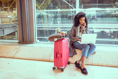 Femme à l'aide du téléphone portable et de l'ordinateur portable à l'aéroport se reposant au Th Images libres de droits