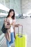 Femme à l'aide du téléphone portable et du bagage à l'aéroport Photos stock