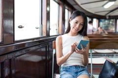 Femme à l'aide du téléphone portable et prenant le ferry en Hong Kong photos libres de droits