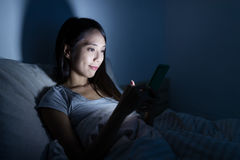 Femme à l'aide du téléphone portable sur le lit photographie stock