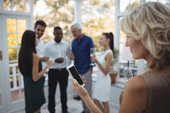 Femme à l'aide du téléphone portable tandis qu'amis agissant l'un sur l'autre à l'arrière-plan Images stock