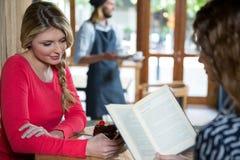 Femme à l'aide du téléphone tandis que livre de lecture d'ami dans le café Photo stock