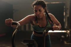 Femme à l'aide du vélo d'exercice au gymnase photos stock