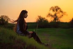 Femme à l'extérieur au coucher du soleil photo stock