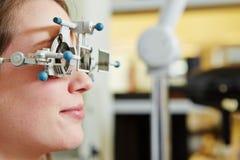 Femme à l'opticien avec le cadre d'essai Photos stock