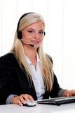 Femme à l'ordinateur avec l'écouteur et la ligne directe Photographie stock libre de droits