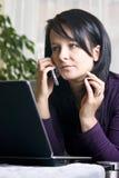 Femme à l'ordinateur portatif et au téléphone images stock