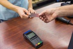 Femme à la caisse enregistreuse payant avec la carte de crédit Photo stock