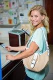 Femme à la caisse enregistreuse payant avec la carte de crédit images stock