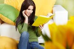 Femme à la maison affichant un livre image libre de droits