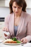Femme à la maison ajoutant le sel au repas photos libres de droits