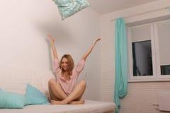 Femme à la maison dans le lit ayant l'amusement et jetant un oreiller Images stock