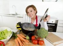 Femme à la maison de cuisinier dans le tablier rouge à la cuisine domestique tenant faire cuire le pot avec le ragoût végétal sen Images libres de droits