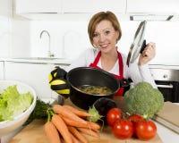 Femme à la maison de cuisinier dans le tablier rouge à la cuisine domestique tenant faire cuire le pot avec le ragoût végétal sen Image libre de droits