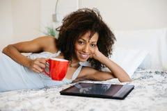 Femme à la maison lisant sur le comprimé numérique images stock