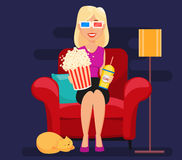 Femme à la maison s'asseyant sur le fauteuil confortable et le film de observation Photos libres de droits