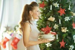 Femme à la mode avec des plats de portion près d'arbre de Noël image stock