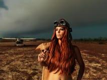 Femme à la mode d'aviateur avec l'avion de smokey Image stock