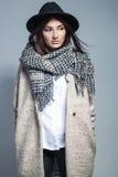 Femme à la mode dans le manteau, l'écharpe de laine et le chapeau posant dans le studio au-dessus du fond gris Images stock