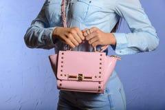 Femme à la mode dans les jeans et la chemise de denim avec le sac à main rose Photos libres de droits