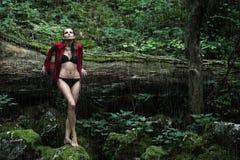 Femme à la mode dans une forêt foncée près de rivière Photos stock