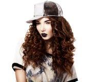 Charme. Mannequin rouge chic de cheveux dans le chapeau futuriste. Maquillage lumineux Photos libres de droits