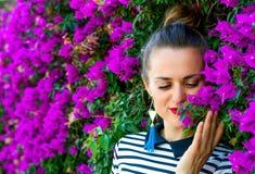 Femme à la mode de sourire appréciant les fleurs magenta colorées Photographie stock