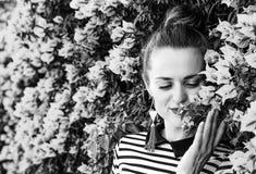 Femme à la mode de sourire appréciant les fleurs magenta colorées Photos libres de droits