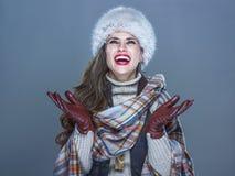 Femme à la mode de sourire d'isolement sur les flocons de neige contagieux bleus froids Photographie stock libre de droits