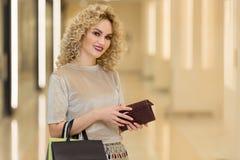 Femme à la mode habillée avec des paniers dans le mail Jeune fille élégante avec le portefeuille photographie stock libre de droits