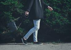 Femme à la mode portant le manteau, les jeans, les espadrilles et le noir noirs Photo libre de droits