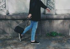 Femme à la mode portant le manteau, les jeans, les espadrilles et le noir noirs Image stock