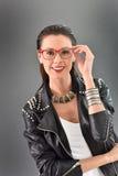 Femme à la mode posant sur le fond gris Photographie stock