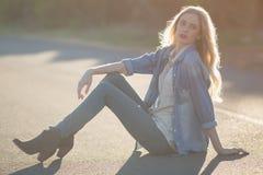 Femme à la mode s'asseyant sur la route et la pose Photo stock