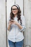 Femme à la mode songeuse avec les verres élégants envoyant le message textuel image stock