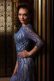 Femme à la mode tenant la colonne proche d'or Photographie stock