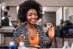 Femme à la peau foncée de sourire avec les cheveux bouclés démontrant un nouvel échantillon de fard à paupières images libres de droits