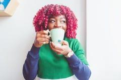 Femme à la peau foncée habillée dans des vêtements sport tenant la tasse de la boisson chaude, appréciant le café ou le thé images stock