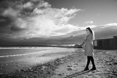 Femme à la plage avec un long manteau photographie stock