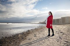 Femme à la plage avec un manteau rouge Photo stock