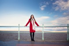 Femme à la plage avec un manteau rouge Photo libre de droits