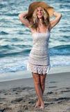 Femme à la plage dans une robe Photographie stock libre de droits