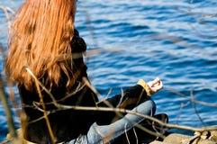 Femme à la pose de yoga au lac photographie stock libre de droits