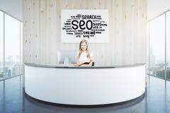 Femme à la réception avec l'affiche de SEO Photo libre de droits