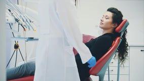 Femme à la réception d'un dentiste dans une clinique dentaire Elle s'assied dans une chaise rouge Avec crainte d'un patient regar clips vidéos